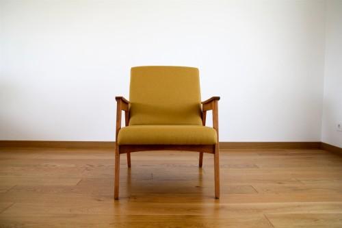 Geltonas danų dizaino krėsliukas.